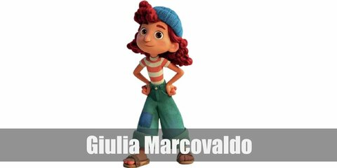 Giulia's costume is an orange and white striped shirt, denim pants with a patch, and a blue knit beanie atop her curly red hair.