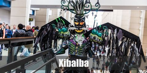 Xibalba's costume includes a long sleeved top with vest paired with a long skirt. It is styled with neon details and a feathered shoulder to match the wings. Finish the look with black gloves and a black mask.