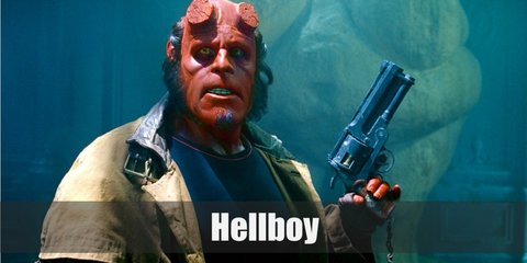 Hellboy's costume is two horn stumps on his head a red forked tail. He wears a black shirt, a beige trench coat, black cargo pants, and black boots.