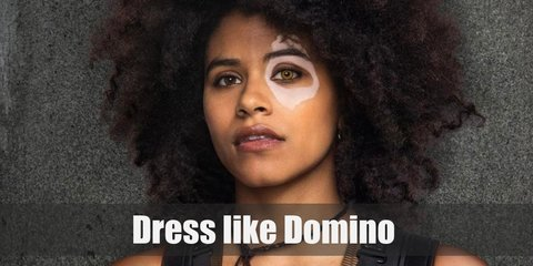 Domino's appearance in the movie is drastically different from the comics. In the movie, she has beautiful, crazy brunette hair. She wears a sleeveless, black leather top, a pair of black leather pants, and a pair of knee-high boots.