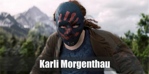 Karli Morgenthau's costume is a blue camo top, a brown bomber jacket, cargo pants, and the Flag Smasher mask.