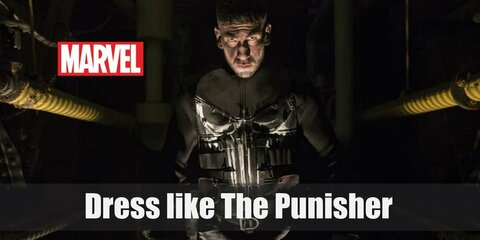 The Punisher wears a black long-sleeved top with a white skeleton printed in the front, black tactical pants, tactical belt, long black trench coat, and combat boots.
