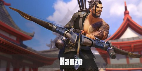 Hanzo wears a grey yukata top and shorts with boots designed with metallic accents. He has a blue cloth at the waist with a fanny pack. He has a gauntlet on one hand and his exposed shoulder has tattoos.