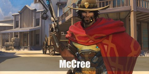 McCree costume inclues an armor on his chest draped with a red poncho or shawl. He has brown pants styled with a belt with a golden bar, a belt of bullets, and gun holsters. He has metallic gloves and arm guard, brown boots, and a cowboy hat. He carries a metallic gun.