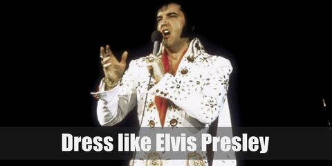 Elvis has had many popular outfits throughout his career, and this outfit is one of his more famous ones. Here he wears an all-white ensemble, with pops of red and glittering details. He sports on his famous sideburns and iconic hairstyle.
