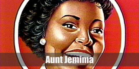 Aunt Jemima wears a red plaid dress, a yellow plaid head scarf, a tied white neck scarf, a white apron, white socks, and black shoes.