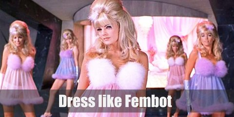 Fembots costume is pink sheer chemise with boa feathers on the bust and hems, a matching pink pair of gloves, step-ins with feathers, and blonde hair in a beehive updo with a feather hair accessory.