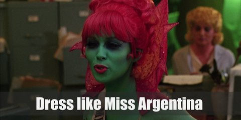 Miss Argentina has green-tinged skin with blindingly red hair put up in an elegant updo. She also wears a sexy strapless dress and a sheer red cape.