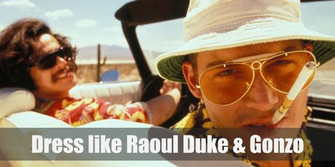 Raoul Duke wears a black and yellow Hawaiian shirt, khaki pants, a white bucket hat, and yellow aviators. Dr. Gonzo wears a red Hawaiian shirt, khaki pants, and black sunglasses.