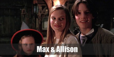 Max's costume is a blue sweatshirt, denim pants, and a bomber jacket. Allison's costume is a white sweater, a beige cardigan, and denim jeans.