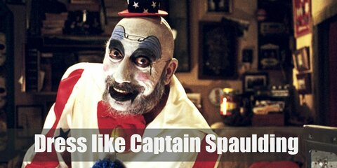 Captain Spaulding wears a white crown shirt with bow tie and red-stripe sleeves, American flag pants, a tiny patriotic hat, and red shoes.