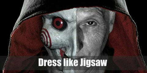 John Kramer or Jigsaw wears a long black robe with red inner hood, a gray T-shirt, black pants, black gloves, and black boots.
