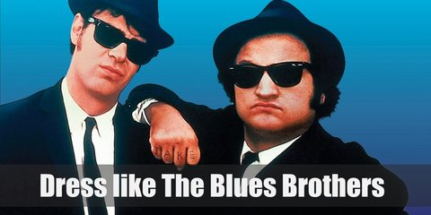 The Blues Brothers were known for their super simple get-up. They both wear white dress shirts underneath black suits, black neck ties, black Oxfords, black glasses, and black Fedoras.