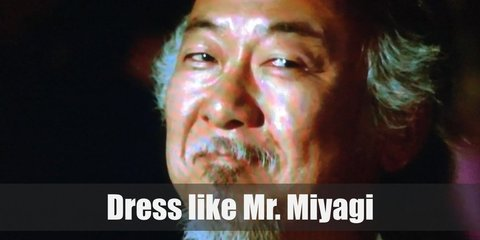 Mr. Miyagi wears a monochrome outfit. He has on a long-sleeved khaki button-down shirt, a pair of khaki pants, black shoes, and a Miyagi Dojo headband.