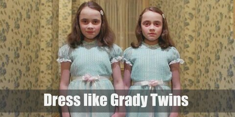 The Grady Twins wear the same dress and look identical to the last detail. The twins both wear innocent-looking light blue Sunday dresses, white stockings, and black Mary Janes.