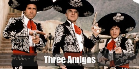 The Three Amigos costume include a mariachi-inspired ruffled top, jacket, and pants with a red bow and sash. They also wear a sombrero or a wide hat.