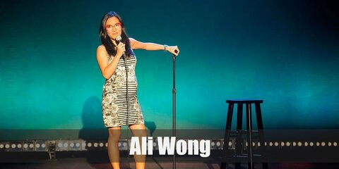 Ali Wong's costume features a baby bump and a black and white striped dress. The costume is accentuated with a pair of red eye glasses and red flat shoes.