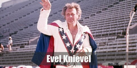 Evel Knievel's costume is a white jumpsuit and a white cape with blue and red details as well as a white pair of shoes. Don't forget his helmet!