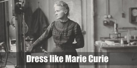 Marie Curie costume is a black conservative long-sleeved gown with a high crew neckline. Her hair is tied in a messy bun. She also wears a minimalist necklace.