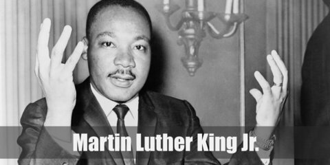 Martin Luther King's costume consists of a practical white top and pants layered with a jacket. He also wears dark shoes. Complete the costume with a bald wig or hair net.