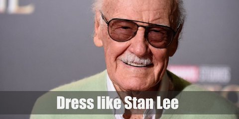 Stan Lee costume is wearing a white polo shirt underneath a blue knit sweater, khaki pants, and white sneakers.