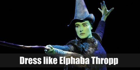 Elphaba costume  is unnaturally green skin, and wearing old-fashioned, dark colored clothes and a pointy witch's hat.