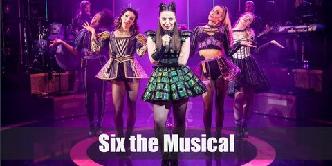 Anne Boleyn's costume in Six the Musical, is a green sleeveless dress with black gaffer tape details, black fishnet tights, black forearm sleeves, black platform boots, a gold 'B' necklace, and spiked hair cuffs.