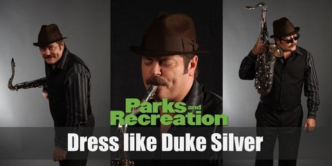 Duke Silver wears a red shirt underneath a grey 3-piece suit, a black fedora, and a pair of black Oxfords while he holds his precious gold saxophone.