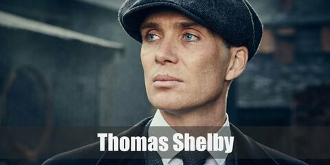 Thomas Shelby's costume is a white dress shirt, a grey three-piece suit, black Oxfords, a bronze tie, a black trench coat, a black baker boy's hat, and a pocket watch.