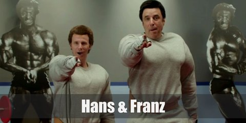 Hans and Franz both wear the same outfit. They have on a grey sweater, grey sweatpants, black boots, and a beige belt. They also use fake muscle suits to look super buff.