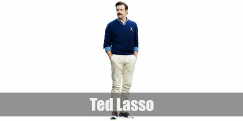 Ted Lasso's costume is a light blue Oxford shirt under a dark blue sweater, khaki pants, and dark sneakers.