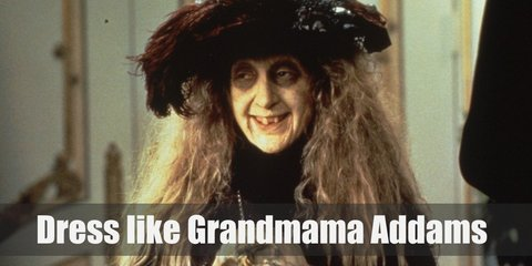 Grandmama Addams costume is wearing a black dress, black and white tights, a black hat, and black boots.
