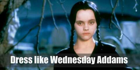 If you look past her creepy look, Wednesday Addams actually has a pretty nice fashion style going on. She wears a black Peter Pan collared dress, black tights, and black shoes. Her long black hair is also done in two braids.