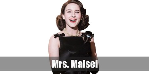 Mrs. Maisel most famous costume is her hot pink outfit that consists of a maroon dress, pink coat, and hot pink gloves.