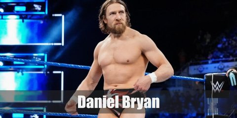 Daniel Bryan wears red-and-black trunks with matching wrestling boots. Wear skintone shirts with this costume. He has long, unkempt hair and facial hair, too.